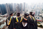 Group of graduates will face the modern city — Stock Photo