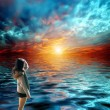Beautiful young woman looked with delight at the sea and sky on sunset — Stock Photo #26301547