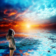 Beautiful young woman looked with delight at the sea and sky on sunset — Stock Photo