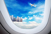 Through the aircraft windows, Higher than the clouds of skyscrapers, exaggerated performance — Stock Photo