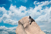 Young man climbing on a limestone wall with blue sky on the background — Stock Photo
