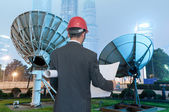 Backside of man and antenna against blue sky — Stock Photo