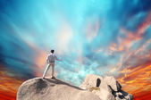 Young man standing on cliff's edge and looking into a wide valley — Stock Photo