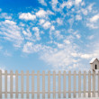 White fence with bird house and blue sky — Stock Photo #27494717