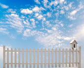 White fence with bird house and blue sky — Stock Photo