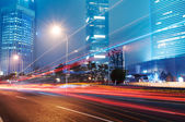 The light trails on the modern building background in shanghai china. — Stockfoto