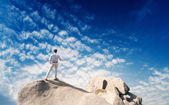 Young man standing on cliff's edge and looking into a wide valley — Photo