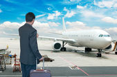 Busines person and plane on the background against cloudy sky — Stock Photo