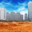 A city looks over a desolate cracked earth landscape — Stock Photo