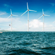 Stock Photo: White wind turbine generating electricity on sea