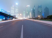 Asphalt road and modern city — Stock Photo
