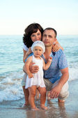 Happy pregnant family with a daughter on the beach. — Stock Photo