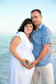 Pregnancy. Young loving couple on the beach. — Stock Photo