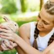 Cute little girl with a rabbit in the garden. — Stock Photo