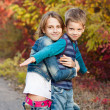 Young sister with little brother in the autumn park. — Stock Photo