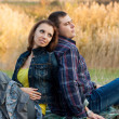 Loving couple sitting on the grass in the autumn garden. — Stockfoto