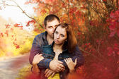 Loving couple in the autumn garden. — Stock Photo