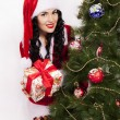 Beautiful Santa Girl with gifts near fir tree — Stockfoto