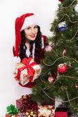 Köknar ağacı yakınındaki hediyeler ile güzel bir noel baba kız — Stok fotoğraf