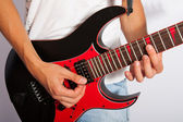 Man playing a guitar in studio. Close up. — Stock Photo