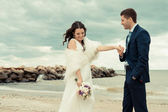 Happy newlyweds are walking near the seashore — Stock Photo
