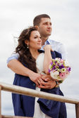 Loving bride and groom standing on the pier — Stock Photo