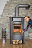 Child opening wood fired stove — Stock Photo
