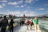 A tourist photographs St Paul's Cathedral from the London Millennium Footbridge, Bankside, London, UK — Stock Photo