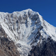 Kyrgyzstan - snow avalanche falling from Chapaev Peak (6731m) . — Stock Photo