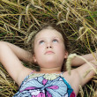 Cute girl lying in a field and dreaming - Stock Photo