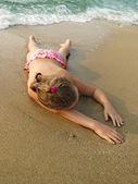 Cute young girl lying on a sandy beach — Stock Photo