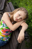 Beautiful young girl is sitting on the bench — Stock Photo
