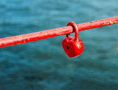 Red padlock in the form of heart on fence — Stock Photo