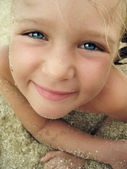 Close-up portrait of smiling little girl on the beach — Stock Photo
