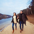 Young couple is running on the beach — Stock Photo