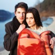 Boy and girl standing near water in warm clothes. - Стоковая фотография