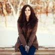 Girl witting on a bench in cold park - Stock Photo