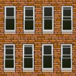 Stock Vector: Seamless brick wall withl windows, background.