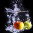 Stock Photo: Two apples makes bubbles, isolated with black background