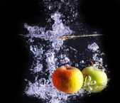 Two apples makes bubbles, isolated with black background — Stock Photo