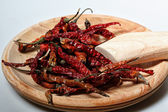 Dry red chilies and wooden grinder, white back ground — Stock Photo