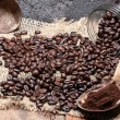 Pouring coffee beans on jute, stone background — Stock Photo
