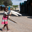 Stock Photo: Local little girl carrying chair in NamibiVillage
