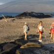 Tourists with sea lion on Galapagos islands - Stock Photo