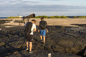 Tourists with camera on volcanic Galapagos terrain — Stock Photo