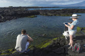 Tourist taking picture of sea lion on Galapagos islands — Stock Photo