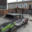 Pimped car on the street with old wooden houses, Irkutsk, Russia - Stock Photo