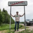 Taking picture by the road sign of village Buhalovo, meaning in russian heavy drinking — Foto Stock