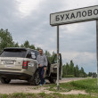 Taking picture by the road sign of village Buhalovo, meaning in russian heavy drinking — Stock fotografie
