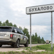 Taking picture by the road sign of village Buhalovo, meaning in russian heavy drinking — Stok fotoğraf